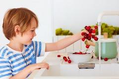 Милый молодой мальчик моя охапку сладостных вишен под водой из крана в кухне Стоковые Изображения RF