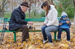 Милый молодой мальчик сидя на скамейке в парке держа планшет пока его мать и дед играют шахмат Стоковая Фотография