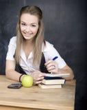 Милый молодой студент около классн классного с ручкой калькулятора книги экземпляра, космосом экземпляра Стоковое Фото