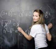 Милый молодой студент около классн классного с ручкой калькулятора книги экземпляра, космосом экземпляра Стоковые Фото