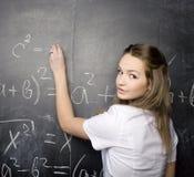 Милый молодой студент около классн классного с ручкой калькулятора книги экземпляра, космосом экземпляра Стоковая Фотография