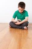 Милый мужской ребенк сидя на поле с таблеткой Стоковые Фотографии RF
