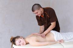 Милый мужской терапевт массажа делает восстанавливать процедуру для задней части  Стоковое фото RF