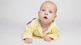 Милый младенец в желтой рубашке лежа на животе видеоматериал
