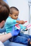 Милый младенец в зубоврачебном стуле стоковая фотография