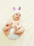 Милый младенец в связанной шляпе при уши кролика лежа на доме кровати Стоковое фото RF