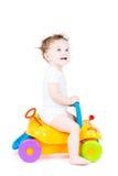 Милый младенец с вьющиеся волосы на автомобиле игрушки стоковая фотография rf
