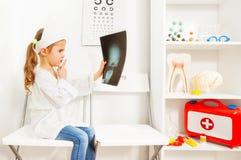 Милый доктор в белизнах и крышка держа рентгеновский снимок черепа Стоковое Изображение