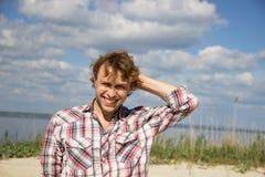 Милый парень в рубашке шотландки смеется над его обхватыванной головой Стоковые Изображения