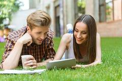 Милый парень и девушка имея потеху на лужайке Стоковые Фото