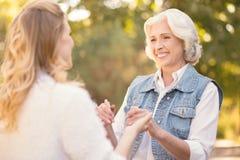 Милый пенсионер держа руки с внучкой в парке Стоковые Фотографии RF