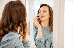 Милый покупатель молодой женщины в голубом платье смотря зеркало стоковое фото rf