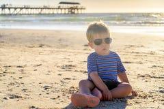 Милый ребенк сидя на пляже Стоковые Изображения