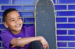 Милый ребенк усмехаясь outdoors с скейтбордом Стоковое Изображение