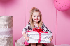 Милый ребенок девушки 3 года старого в платье Младенец держа подарок в их руках Комната розового кварца украсила праздник Стоковое Фото