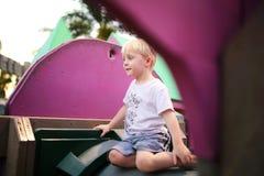 Милый ребенок играя мимо самостоятельно на спортивной площадке Стоковое Фото