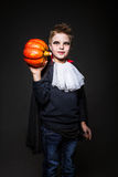 Милый ребенок одетый как вампир для партии и держать хеллоуина оранжевую тыкву стоковое фото