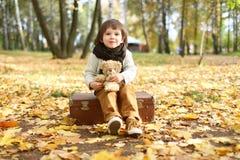 Милый ребенок при медведь игрушки сидя на чемодане в парке осени стоковые фото