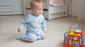 Милый ребёнок вползая на поле на живущей комнате и принимая игрушку видеоматериал