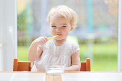 Милый ребёнок есть югурт от ложки Стоковые Изображения