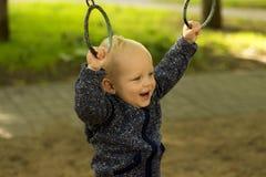 Милый ребёнок делая спорт в парке Смешные разминки малыша на атлетических кольцах стоковое изображение rf