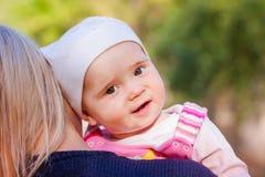 Милый ребёнок смотря вне от задней части матери Стоковые Изображения
