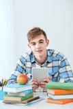 Милый студент используя планшет Стоковые Изображения