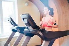Милый сфокусированный спортсмен молодой женщины бежать на третбане в спортзале Стоковая Фотография RF