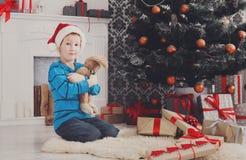 Милый счастливый мальчик в шляпе santa с подарками на рождество игрушки Стоковое фото RF