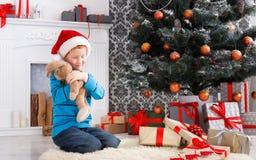 Милый счастливый мальчик в шляпе santa с подарками на рождество игрушки Стоковая Фотография RF
