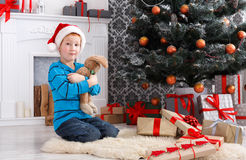 Милый счастливый мальчик в шляпе santa с подарками на рождество игрушки Стоковое Фото