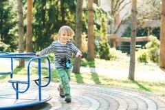 Милый счастливый ребенк Мальчик играя на спортивной площадке в парке стоковые фото