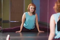 Милый танцор пролома делая разделения смотря в зеркале Стоковые Изображения RF