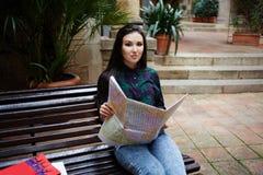 Милый турист девушки смотря на карте трассу к следующему городу Стоковая Фотография