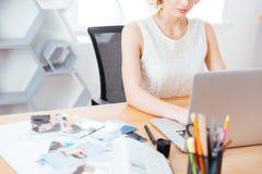 Милый фотограф женщины работая с компьтер-книжкой в офисе Стоковые Фотографии RF