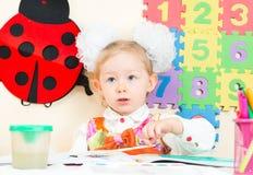 Милый чертеж девушки ребенка в preschool на таблице в детском саде Стоковое фото RF