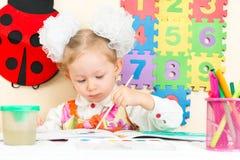 Милый чертеж девушки ребенка в preschool на таблице в детском саде Стоковое Изображение RF