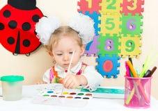 Милый чертеж девушки ребенка рисовал в preschool на таблице в детском саде Стоковое Изображение