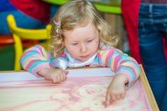 Милый чертеж девушки ребенка рисует превращаясь песок в preschool на таблице в детском саде Стоковое фото RF