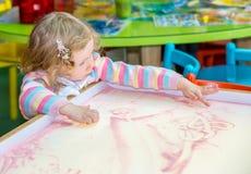 Милый чертеж девушки ребенка рисует превращаясь песок в preschool на таблице Стоковая Фотография RF