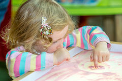 Милый чертеж девушки ребенка рисует превращаясь песок в preschool на таблице в детском саде Стоковые Фотографии RF