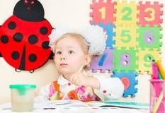 Милый чертеж девушки ребенка с красочными карандашами в preschool в детском саде Стоковая Фотография
