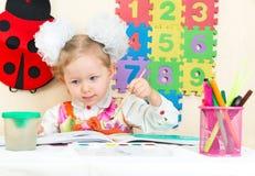 Милый чертеж девушки ребенка с красочными карандашами в preschool в детском саде Стоковое Изображение