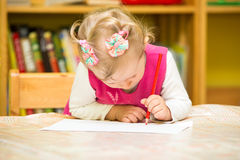 Милый чертеж девушки ребенка с красочными карандашами в preschool на таблице в детском саде Стоковое Изображение