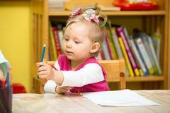 Милый чертеж девушки ребенка с красочными карандашами в preschool на таблице в детском саде Стоковое Фото