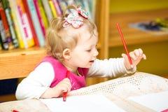 Милый чертеж девушки ребенка с красочными карандашами в preschool на таблице в детском саде Стоковая Фотография