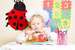 Милый чертеж девушки ребенка с красочными карандашами в preschool на таблице в детском саде Стоковые Фото