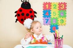 Милый чертеж девушки ребенка с красочными карандашами в preschool на таблице в детском саде Стоковые Изображения