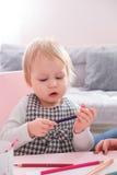 Милый чертеж девушки ребенка с красочными карандашами в preschool на таблице в детском саде Стоковое Изображение RF