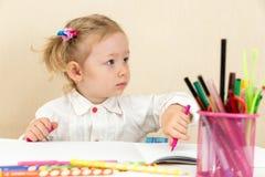 Милый чертеж девушки ребенка с красочными карандашами и ручка войлок-подсказки на таблице в детском саде Стоковые Изображения RF